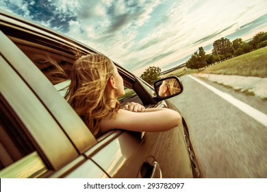 Happy beautiful girl traveling in a car across Europe with focus in front of the car