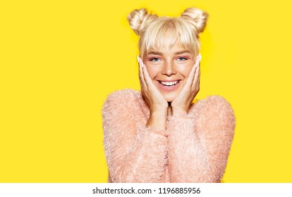 Happy beautiful girl with two buns of hair, dressed in a fluffy pink sweater, laughs and touches her face with her hands. Portrait on a bright yellow background