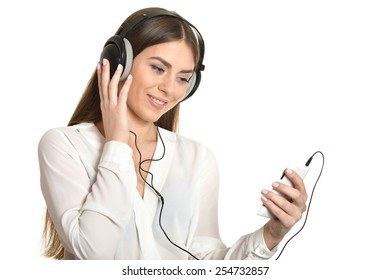 Happy beautiful girl using her mobile phone listening to music with headphones