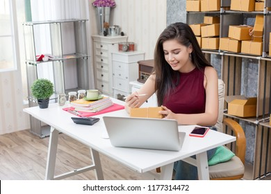 Happy beautiful girl who works at home About Online Business, Prepare goods to customers.