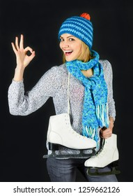 Happy beautiful girl in winter clothes with ice skates shows ok gesture. Ice skating winter woman holds ice skates. Ice skating girl with figure skates. Winter vacation. Sports activity in winter time