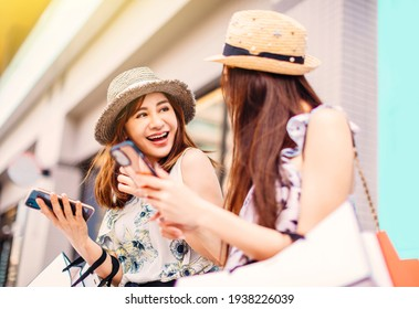 Happy Beautiful girls  holding shopping bags and using the smart phone