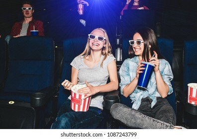 Happy and beautiful girls are sitting in cinema hall and watching movie. Blonde girl is looking straight and smiling while her friend is looking at her with a smile and holding a big cup of cola.