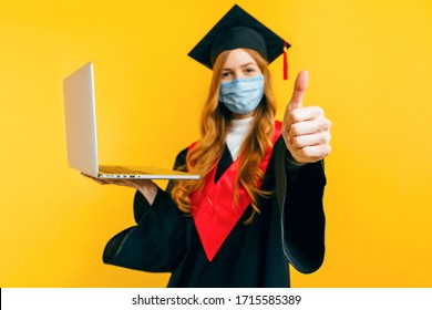 A happy, beautiful graduate, with a medical protective mask on her face, uses a laptop and gives a thumbs-up on a yellow background. Distance learning, quarantine, coronavirus