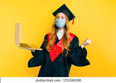 A happy, beautiful graduate, with a medical protective mask on her face, uses a laptop on an isolated yellow background. Distance learning, quarantine, coronavirus