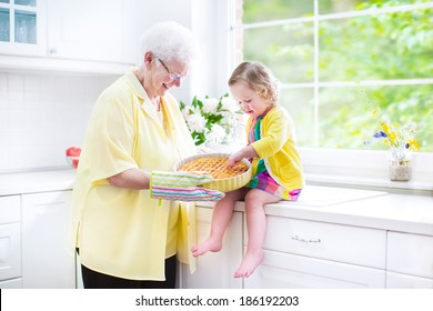 Happy beautiful great grandmother and her adorable granddaughter, curly toddler girl in colorful dress, baking an apple pie together standing next to white oven in sunny modern kitchen with big window