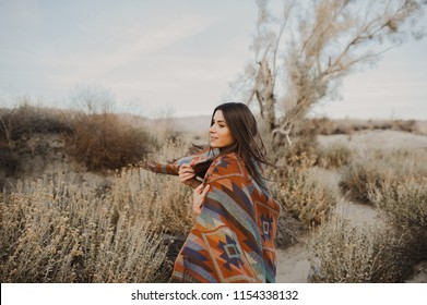 Happy, beautiful hipster traveler girl in gypsy look and windy hair, in desert nature.  Artistic photo of young hipster traveler girl in gypsy look, in Coachella Valley in a desert valley in Souther