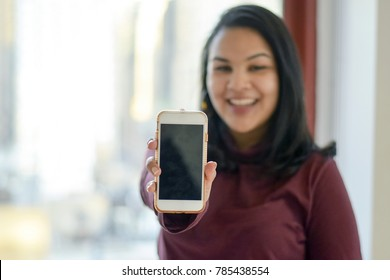 Happy beautiful hispanic woman showing smartphone screen