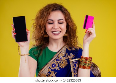 happy beautiful indian female person in traditional dress holding shop credit card and smartphone .black friday sales studio yellow background.