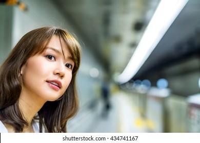 Happy beautiful japanese woman smiling while waiting train at subway station.