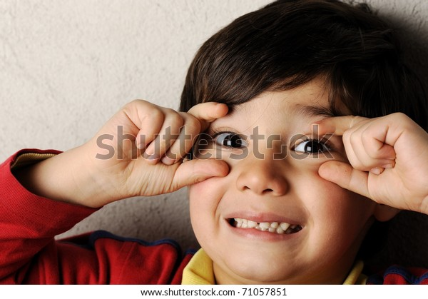 Happy beautiful kid boy with funny face and fingers on his eyes