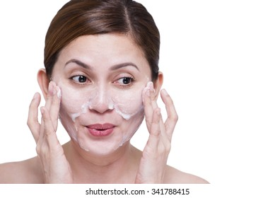 Happy beautiful lady cleaning her face with soap. Isolated in white background.