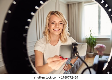 Happy beautiful lady setting her ring light and getting ready for recording herself on a modern smartphone