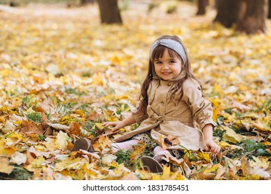 Happy and beautiful little girl in a beige coat sitting among the yellow leaves in the autumn park