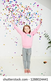 Happy beautiful little girl enjoying colorful confetti surprise falling down, posing on white studio wall. Pretty girl celebrating her birthday party, having fun
