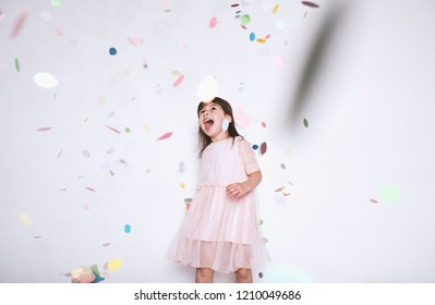 Happy beautiful little girl wearing pink dress with princess crown enjoying colorful confetti surprise falling down, posing on white studio wall. Pretty girl celebrating her birthday party, having fun