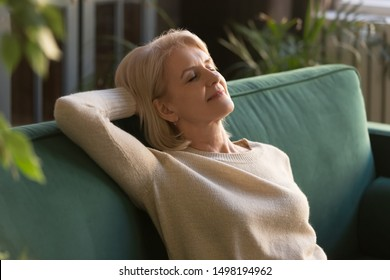 Happy beautiful mature woman rest on comfortable sofa in living room, see dreams visualize, peaceful exhausted elderly grandmother take break breathe air, relaxing on couch napping at home