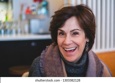 Happy beautiful middle aged woman laughing indoors