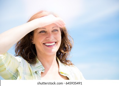 Happy beautiful middle aged woman protecting from sun with hand as a sun visor