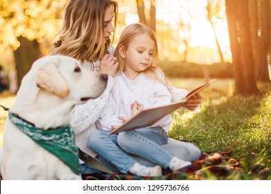 Happy beautiful mother and daughter with dog labrador is reads book sitting in the park.