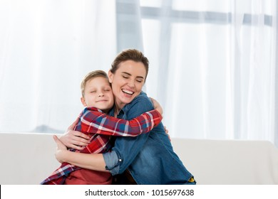 happy beautiful mother embracing with little son
