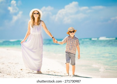 Happy beautiful mother and son walking along the beach in a sunny day