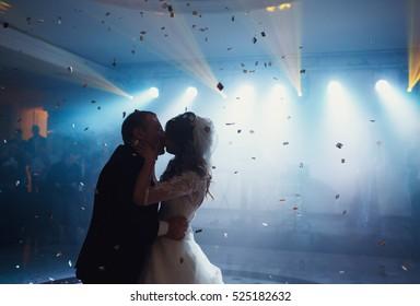 Happy beautiful newlyweds kissing on the dancefloor