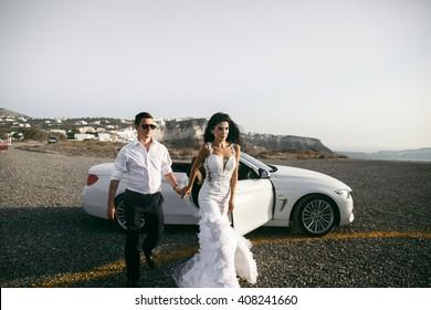 Happy beautiful newlyweds near the car