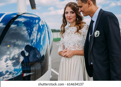 Happy beautiful newlyweds near the helicopter