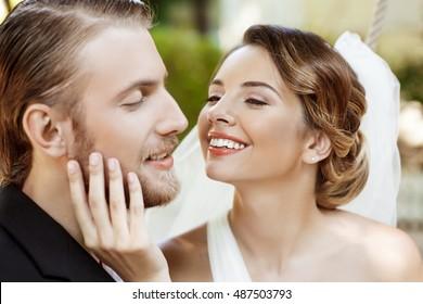 Happy beautiful newlyweds in suit and wedding dress smiling, enjoying.