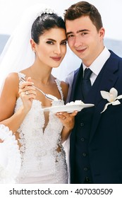 Happy beautiful newlyweds taste a wedding cake