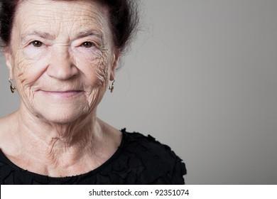Happy beautiful older lady posing on gray background.