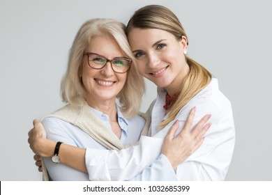 Happy beautiful older mother and adult daughter embracing looking at camera, smiling senior lady hugging young woman, family of different age generations bonding hugging, head shot portrait