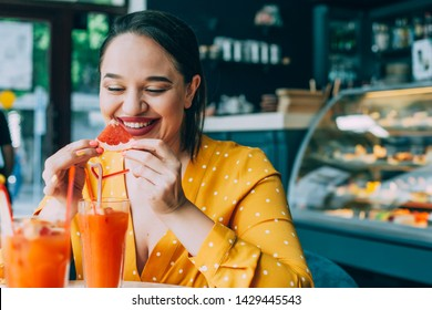 Happy beautiful plus size woman laughing and drinking healthy vegan citrus fruit smoothie in city cafe