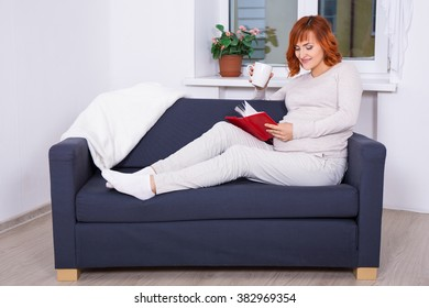 happy beautiful pregnant woman drinking tea and reading book at home