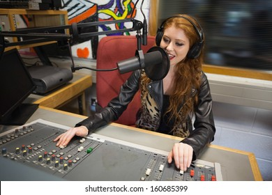 Happy beautiful radio host moderating sitting in studio at college