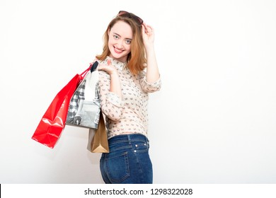 Happy beautiful redhead woman with sunglasses holding her shopping bags against light background and smiling.