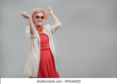 Happy beautiful senior lady wearing sunglasses and hat