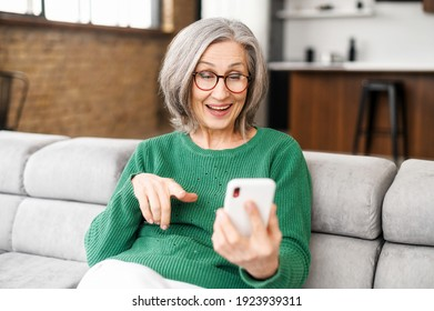 Happy beautiful senior woman is using a smartphone for video calling to family, friends or dating online. Mature elderly lady holds the phone and using app for video communication, online meeting