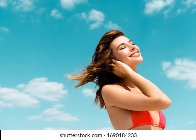 happy beautiful sexy girl in swimsuit on blue sky with clouds background