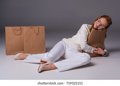 happy beautiful shopaholic in white clothes hugging shopping bags, on grey