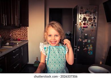 Joyeuse petite fille au tablier cuisinant à la maison