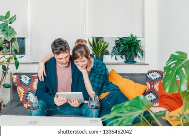 happy beautiful smiling couple at home sitting on a couch and surfing on the internet with a tablet