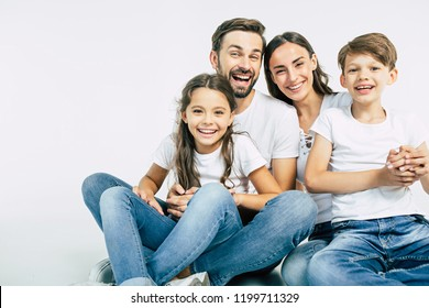 Happy beautiful and smiling dad, mommy and them kids sitting on the floor in white studio isolated