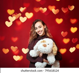 happy beautiful smiling woman with a big toy dog on a red wall background. Valentine's day, mother's day, birthday and a gift