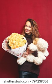 happy beautiful smiling woman with a bouquet of roses and a big toy dog on a red wall background. Valentine's day, mother's day, birthday and a gift