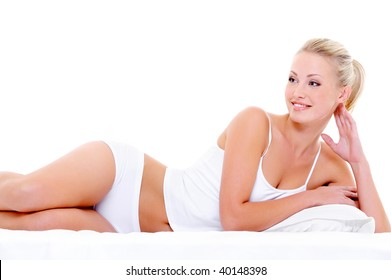 Happy beautiful smiling woman with a sexy body  lying in underwear on the white bed