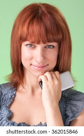 Happy beautiful smiling young woman with red hair talking on cellphone in studio
