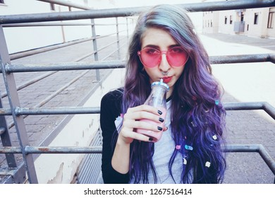 Happy beautiful teen with pink sunglasses drinks and enjoys a pink beverage sitting on urban ground