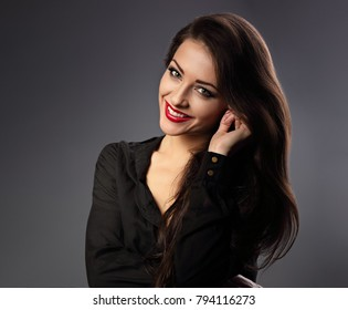 Happy beautiful toothy smiling woman with long hair style in fashion black shirt looking on dark shadow background. Closeup portrait